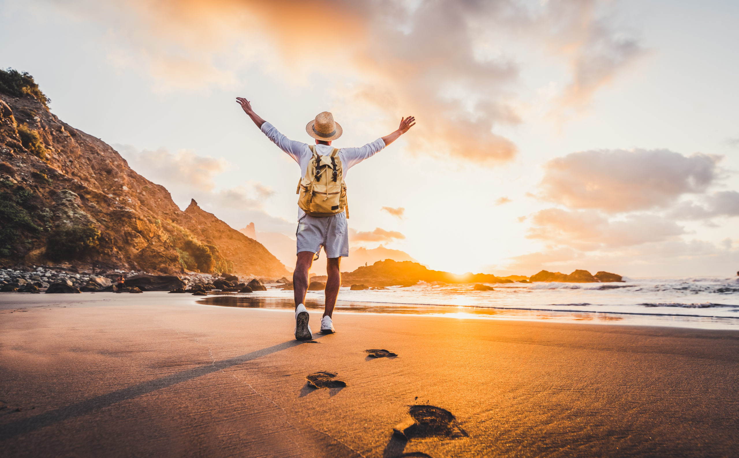 young-man-arms-outstretched-by-sea-sunrise-enjoying-freedom-life-people-travel-wellbeing-concept